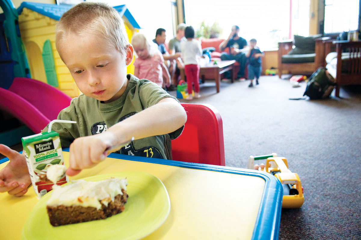 Above, a young patron at Sovereign Grounds in Minneapolis digs into a wedge of carrot cake. At top, customers at Village Bean in Bothell, Washington, enjoy coffee and light reading in the café's play space. (Photo: courtesy Sovereign Grounds.