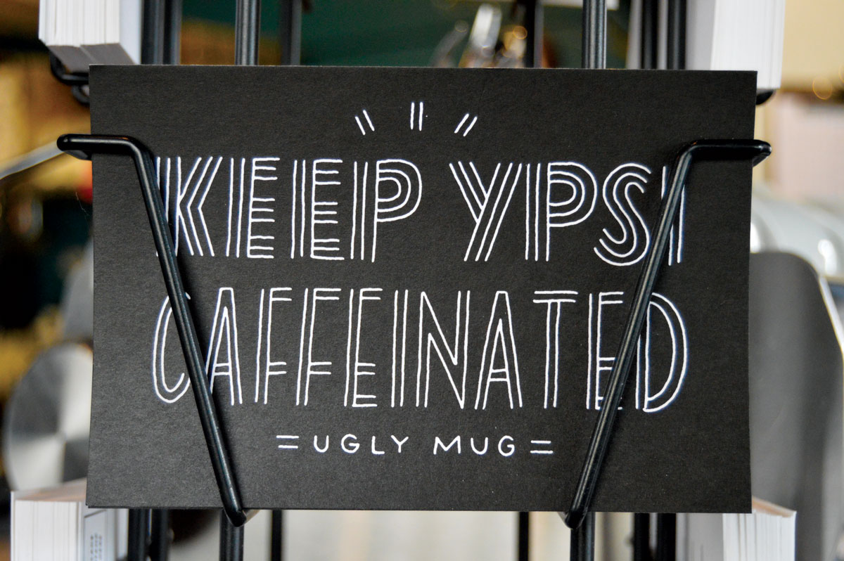 Keep Ypsi Caffeinated postcard by a local printmaker are on sale at the Ugly Mug. (Photos by Jessica Copi.)