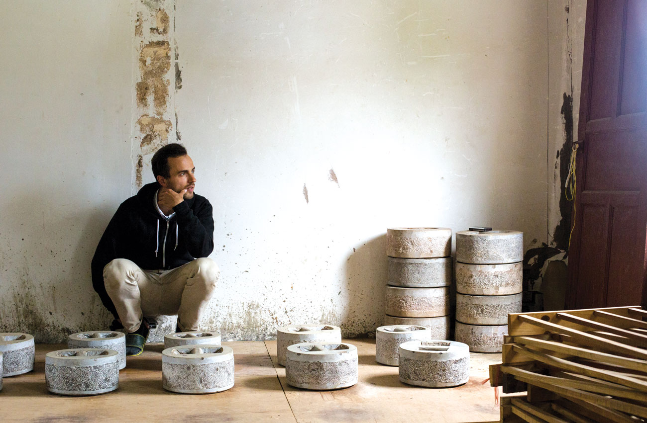 Lozito crouches among the weights that are used to press pu-erh.
