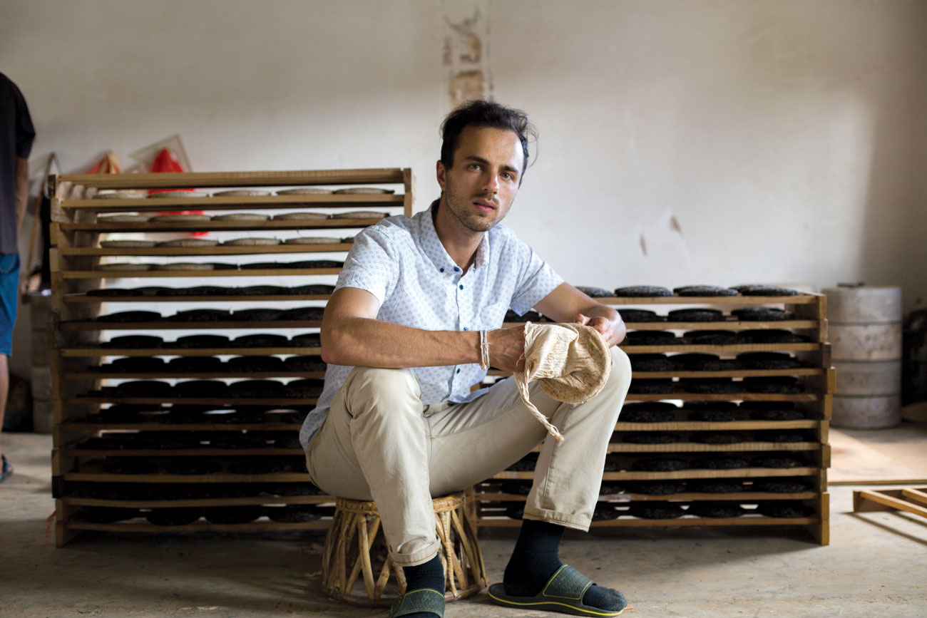 Nicholas Lozito holds a bag in which processed tea leaves are placed and then pressed into bings.
